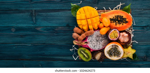 Fruit dragon, papaya, maracuya, kiwi, mango and granadilla in a wooden box. Fresh Tropical Fruits. On a wooden background. Top view. Copy space.