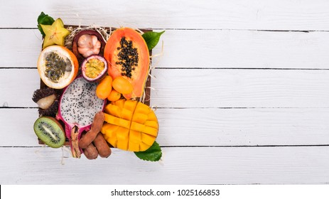 Fruit dragon, papaya, maracuya, kiwi, mango and granadilla in a wooden box. Fresh Tropical Fruits. On a wooden background. Top view. Copy space.