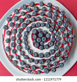 fruit flan with creamy curd, jam spiral decorated with big blueberries. top view.
