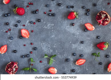 Fruit frame with strawberry, blueberry, pomegranate on black background. Flat lay, top view.