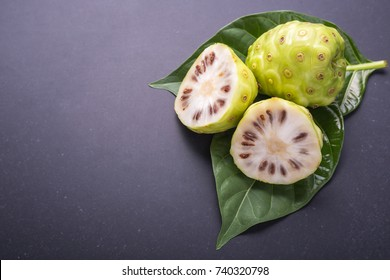 Fruit of Great morinda (Noni) or Morinda citrifolia tree and green leaf on black stone board background