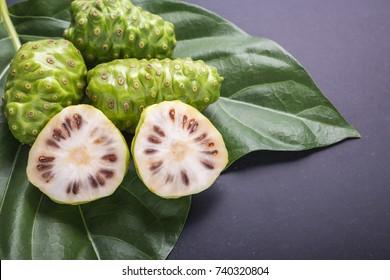 Fruit of Great morinda (Noni) or Morinda citrifolia tree and green leaf on black stone board background