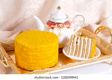 Fruit honey cake and teapot with green tea