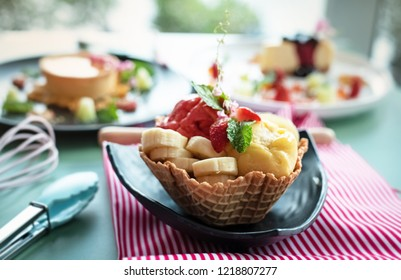 The fruit ice cream with banana,strawberry and mint leaf put in waffle basket,prepare for serving,blurry light around