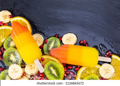 Fruit ice cream on stick with slices fruits on black slate board. Space for text! Focus on Popsicles.