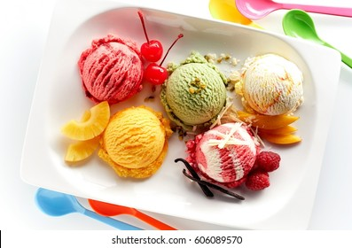 Fruit ice cream scoops overhead on white plate with pieces of fruits and berries, served with several colorful spoons