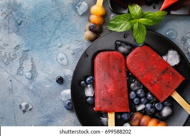 Fruit ice from watermelon, orange and blueberries with mint leaves. Top view of a summer dessert with space for text