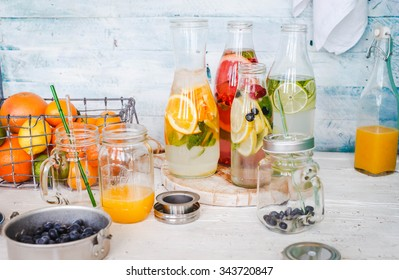 Fruit infused water recipe  in milk bottle with citrus fruits box and blueberry on a white wooden table. Citrus water recipe. Colorful pastel rustic style.
