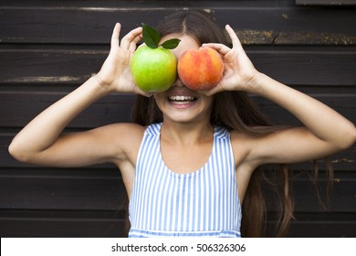 Fruit instead of eyes. Little girl holding a green apple and a peach, summer outdoors