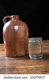 Fruit jar full of moonshine whiskey poured from old brown jug on wooden plank floor with black background.