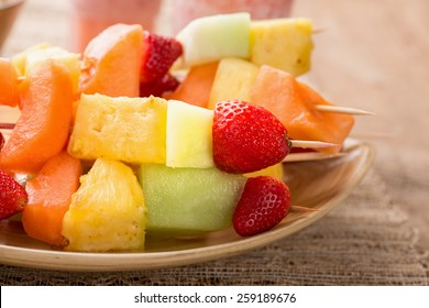 Fruit kabobs - fruit on skewers - on tray with strawberry smoothies