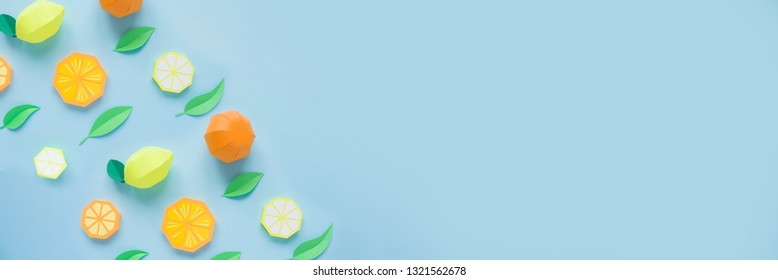 Fruit made of paper. Blue background. There's room for writing. Tropics. Flat lay. Orange, lemon.