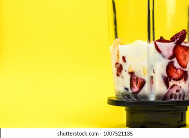 Fruit with milk in a glass blender on the pastel yellow background. Preparation for milk shake making