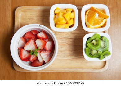 Fruit in the mini cup Starwberry, mango, orange and Kiwi, Fruit salad on the wood tray