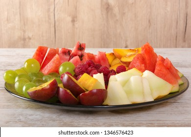 Fruit mix. Peach, grapes, apple, watermelon, melon, raspberry, plum. Pieces of fruit on a plate lie on a white wooden background. Copy space, space for text.