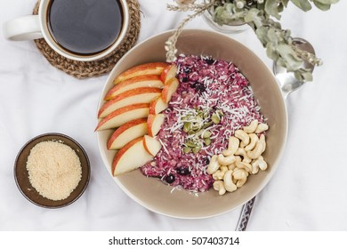 Fruit and Nut Oatmeal Porridge with Brown Sugar and Coffee on White Table cloth with Plant Flat Lay