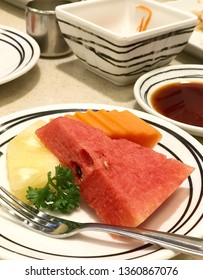 The fruit on a dish. There are a piece of pine apple, watermelon and papaya in Japanese restaurant.