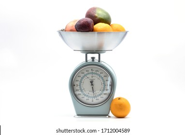 fruit on kitchen food scale on white background