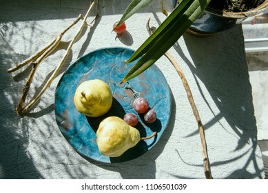 Fruit on an old plate in the sunlight