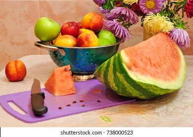 Fruit on the table. Vase with fruit and slices of watermelon on the table.