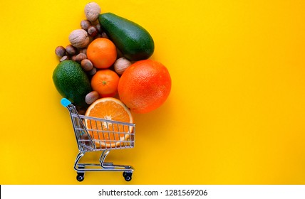 lot of fruit orange, mandarine,avocado and wallnuts ,hazelnuts in the supermarket cart on the yellow background with copy space