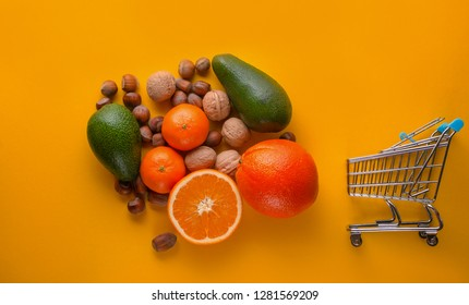 lot of fruit orange, mandarine,avocado and wallnuts ,hazelnuts and supermarket cart on the yellow background with copy space