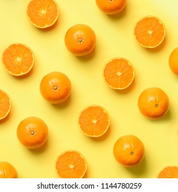 Fruit pattern of fresh orange slices on yellow background. Top view. Copy Space. Pop art design, creative summer concept. Half of citrus in minimal flat lay style. Square crop.