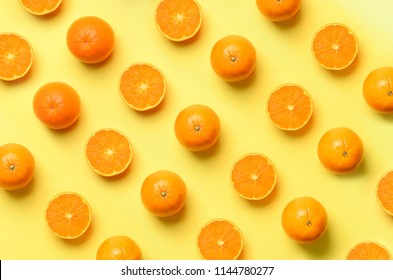 Fruit pattern of fresh orange slices on yellow background. Top view. Copy Space. Pop art design, creative summer concept. Half of citrus in minimal flat lay style