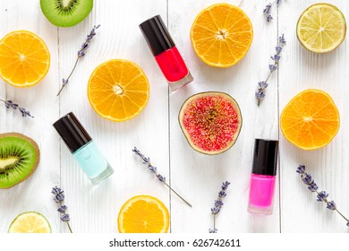 Fruit pattern with lipstick and nailpolish on white desk background top view