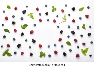 Fruit pattern made of fresh berries and green leaves on white background. Flat lay, top view.