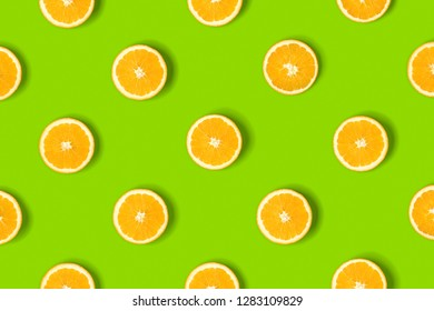 Fruit pattern of orange slices on green background. Flat lay, top view. Food background.