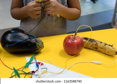 Fruit piano with kids. STEM education activity allow kids to play music with fruit and vegetables. Microcontroller converts keys in sound with some fruits. Yellow background and vegetables wired