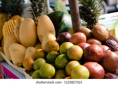 a lot of fruit in the pile are for sale in a street shop in the range of mango, passion fruit, lime, tangerines, watermelon, pineapple