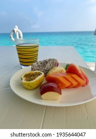 Fruit plate an a glass of orangejuice at the turquoise sea
