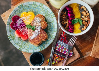 Fruit plate with granola. Exotic fruits. Girl's healthy breakfast. Smoothie bowl with pancakes who make shape of hearts