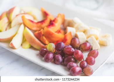 A fruit plate with grapes and slices of apples, bananas and nectarines. The white square plate is on a white marble background and there is lots of light in the photo.