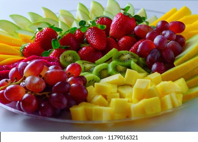 Fruit platter with fresh grapes, apple, pineapple, kiwi, mango, red ripe strawberry and pitaya. Colorful Fruit tray best health good food for party and holidays table.