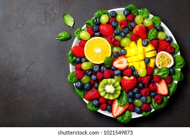 Fruit platter with various fresh strawberry, raspberry, blueberry, tangerine, grape, mango, spinach on a dark black stone background. Copy space, top view, horizontal image