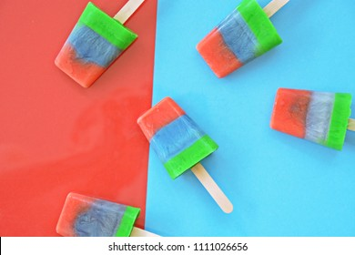 Fruit popsicle / ice cream on blue and red background / Soda and Strawberry and apple popsicle / ice cream stick on blue and red background