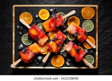 Fruit popsicles, homemade fruit ice lolly of various fruits; mandarins, limes, blackberries, blueberries, raspberries and strawberries with the addition of lemonade on a black background, top view.