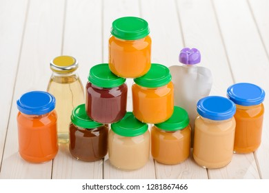 Fruit puree and juice. Portable baby food packaged in jars and pouches on wooden table.