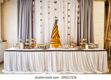 Fruit pyramid decoration, cakes and cookies at dessert table at party in restaurant. Focused on fruit pyramid