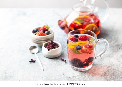 Fruit red tea with berries in glass cup on white background