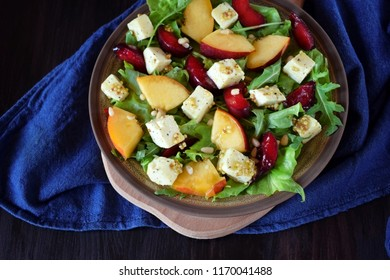 Fruit salad with arugula, plums, nectarines and soft cheese on a plate