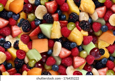 Fruit salad background as fresh berries and cut fruits as blueberry blackberry strawberries melon cantaloupe raspberry pineapple banana and grapes as a symbol of healthy lifestyle and living well.