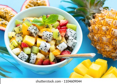 Fruit salad in bowl on blue background. Exotic tropical fruit salad. Dragon fruit, passion fruit, mango, coconut, strawberry and pineapple salad in a bowl