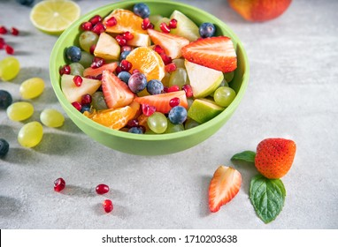 Fruit salad in a bowl on gray surface or table