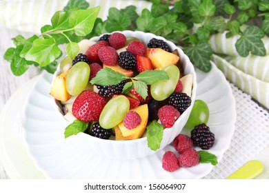 Fruit salad in bowl, on wooden table background
