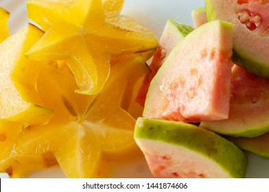 Fruit salad with carambola, carambola and organic guava on white plate, slices of carambola and red guava, red guava fruit salad.  Star fruit.
