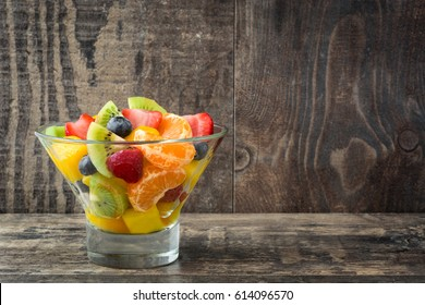 Fruit salad in crystal bowl on wooden table.Copyspace